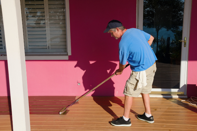 Worker painting staining wooden deck